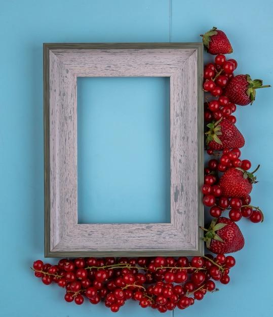 トップビューコピースペースグレーフレームイチゴと明るい青の背景に赤スグリ 無料写真