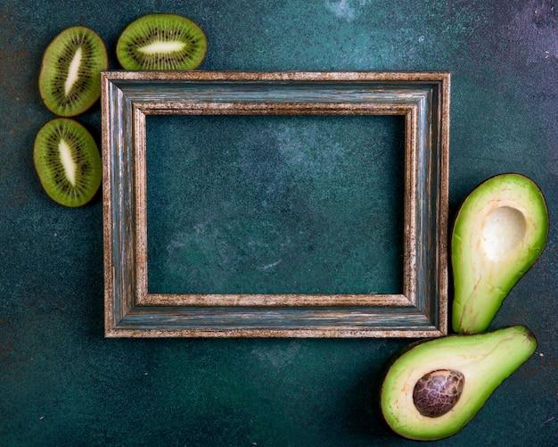 Vista dall'alto copia spazio cornice verde-oro con metà avocado e fette di kiwi su uno sfondo verde scuro Foto Gratuite