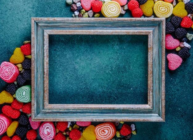 Vista dall'alto copia spazio cornice verde-oro con marmellata multicolore in diverse forme con cioccolatini a forma di pietra su uno sfondo verde scuro Foto Gratuite