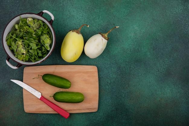 平面図は、ナイフと緑の背景に白いナスとまな板の上にキュウリと鍋のスペースグリーンをコピーします 無料写真