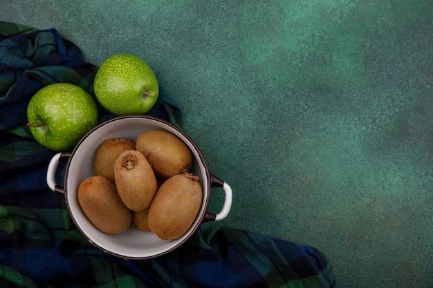 Вид сверху копией космического киви в кастрюле с зелеными яблоками на клетчатом полотенце на зеленом фоне Бесплатные Фотографии