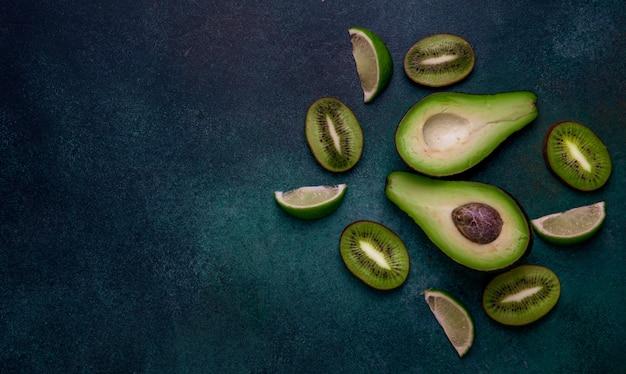 トップビューコピースペースキウイスライスアボカド半分と濃い緑色の背景にライムスライス 無料写真