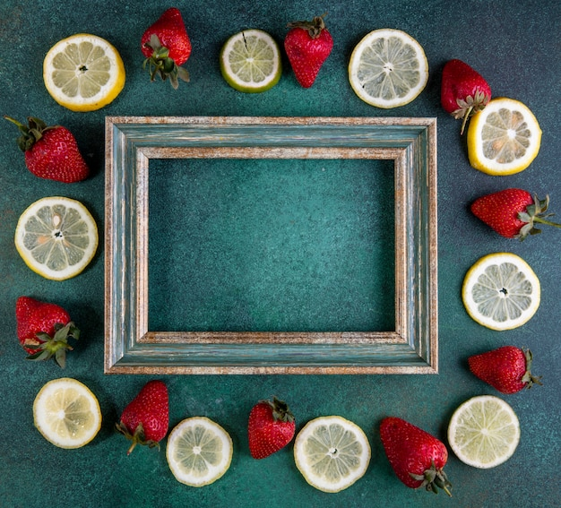 Top view copy space lemon slices and lime with strawberries around the frame on green Free Photo
