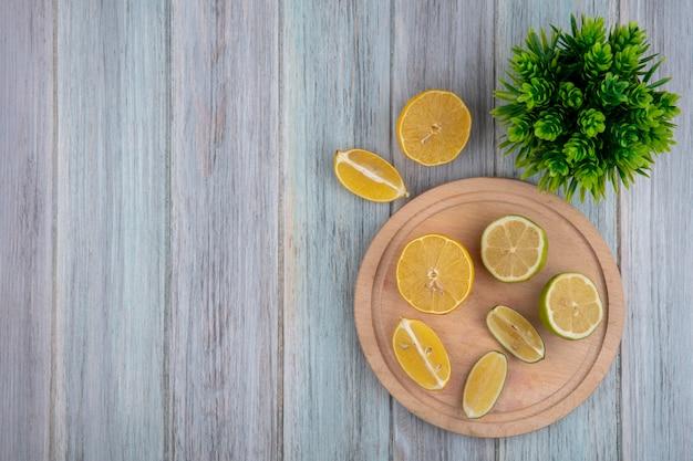 Вид сверху копией пространства дольками лимона с лаймом на разделочной доске на сером фоне Бесплатные Фотографии
