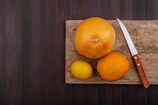 木の背景にナイフでまな板にオレンジとグレープフルーツとレモン 無料写真