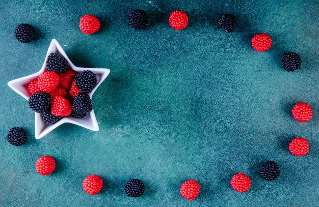 Top view copy space marmalade in the form of blackberries and raspberries in a socket for jam in the shape of a star on a dark green background Free Photo