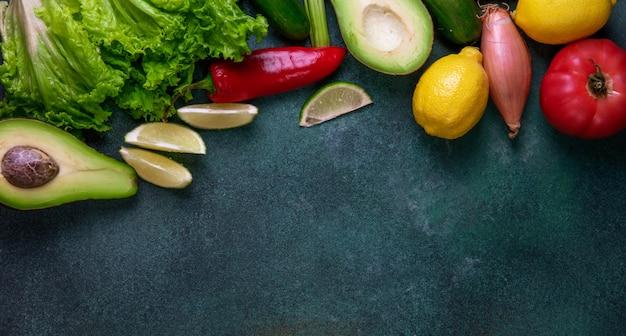 濃い緑色の背景に野菜アボカドレモン赤唐辛子玉ねぎとレタスの平面図コピースペースミックス 無料写真