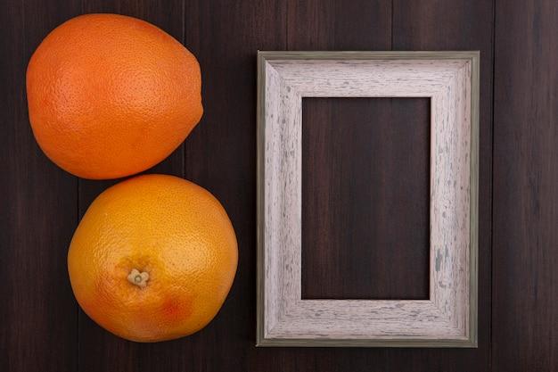 Vista dall'alto copia spazio arance con cornice grigia su sfondo di legno Foto Gratuite