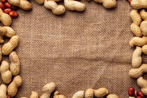 Вид сверху копия пространства арахиса в скорлупе и с очищенным арахисом на фоне мешковины Бесплатные Фотографии