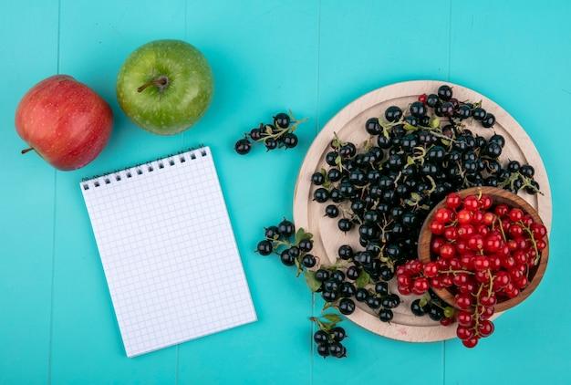 Vista dall'alto copia spazio ribes rosso in una ciotola con ribes nero su una lavagna con un taccuino e mele su uno sfondo blu chiaro Foto Gratuite