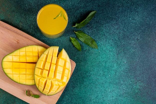 Вид сверху копировать пространство нарезанный манго на доске со стаканом апельсинового сока и листьев мяты Бесплатные Фотографии