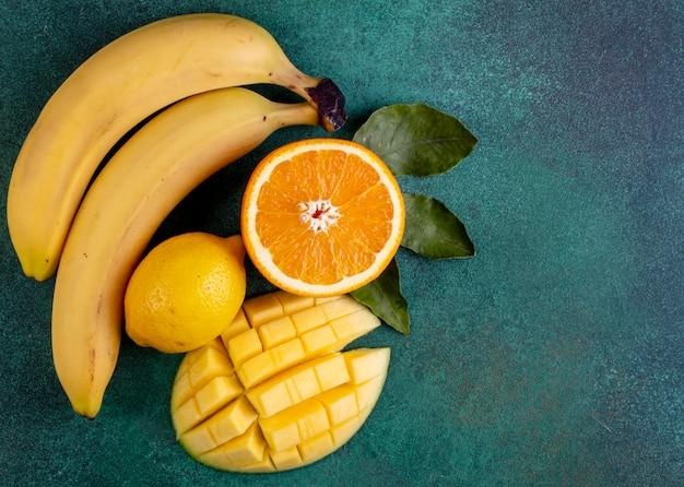 Вид сверху копией пространства нарезанного манго с бананами половиной апельсина и лимоном на зеленом Бесплатные Фотографии