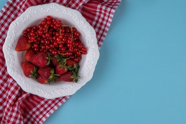 Вид сверху копия космической клубники с красной смородиной на тарелке с красным кухонным полотенцем на голубом фоне Бесплатные Фотографии