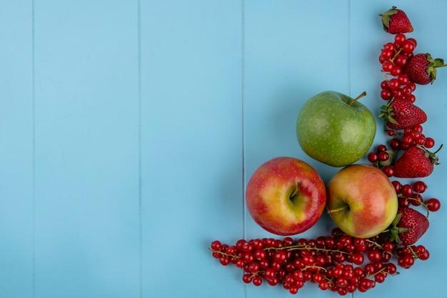 トップビューコピースペースイチゴと赤スグリと明るい青の背景にリンゴ 無料写真