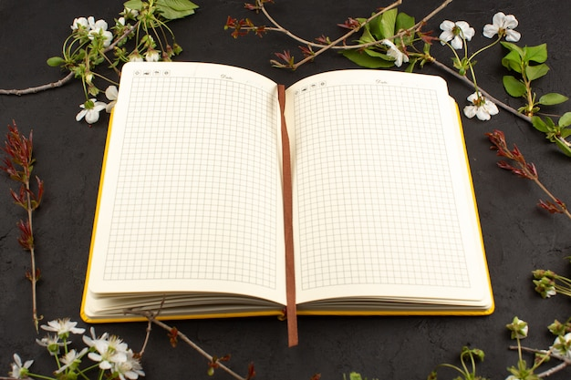 Top view copybook along with white flowers on the dark desk Free Photo