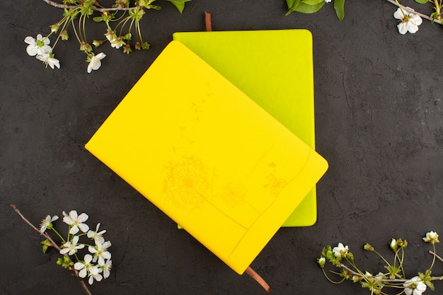 Top view copybooks yellow and mustard colored around white flowers on the dark floor Free Photo