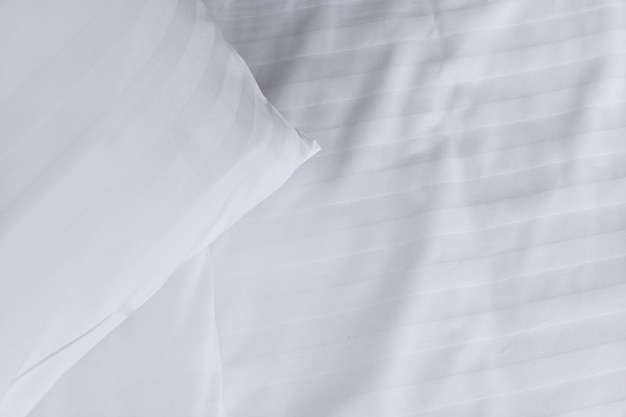 Top view corner of white pillow on white clean bed close up, copy space Premium Photo