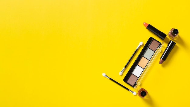 Top view of cosmetics on yellow background with copy space Free Photo