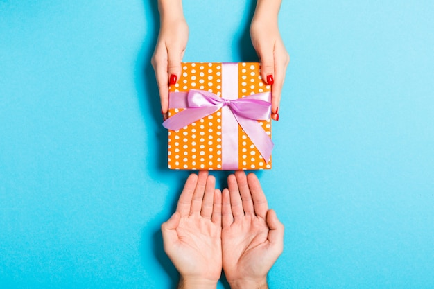 Top view of couple giving and receiving a gift on colorful background Premium Photo