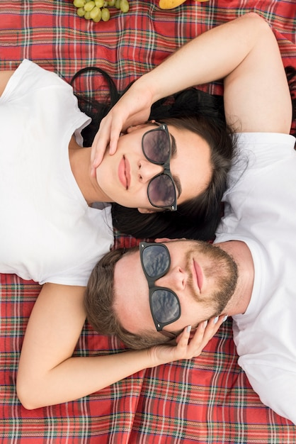 Top view couple laying on picnic blanket Free Photo