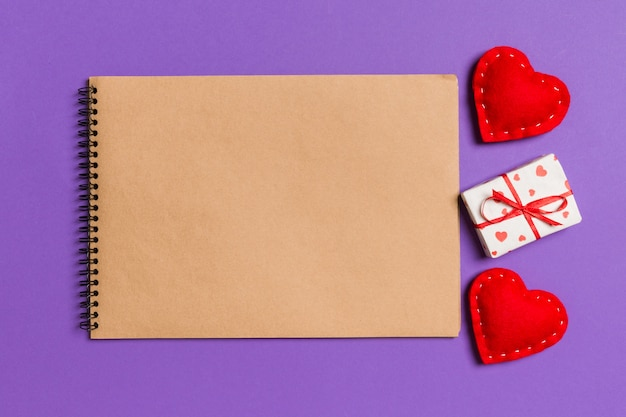 Top view of craft notebook surrounded with gift box and hearts Premium Photo