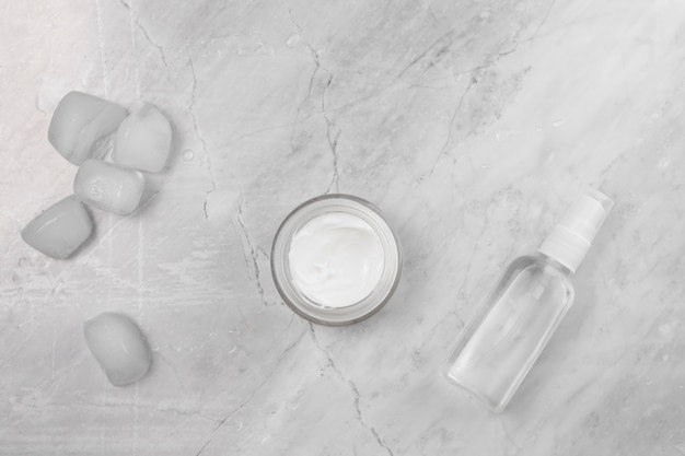 Top view of cream and bottle on marble background Free Photo