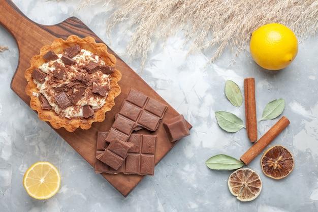 Вид сверху кремовый торт с шоколадными батончиками лимоны на светлом столе сладкий торт сахарный крем шоколадный Бесплатные Фотографии