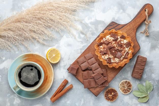 トップビュークリームの小さなケーキとチョコレートバーとライトデスクのお茶甘いケーキシュガークリームチョコレート 無料写真