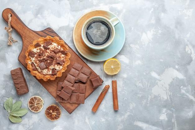 Top view crema piccola torta con barrette di cioccolato e tè sulla scrivania leggera torta dolce crema al cioccolato Foto Gratuite