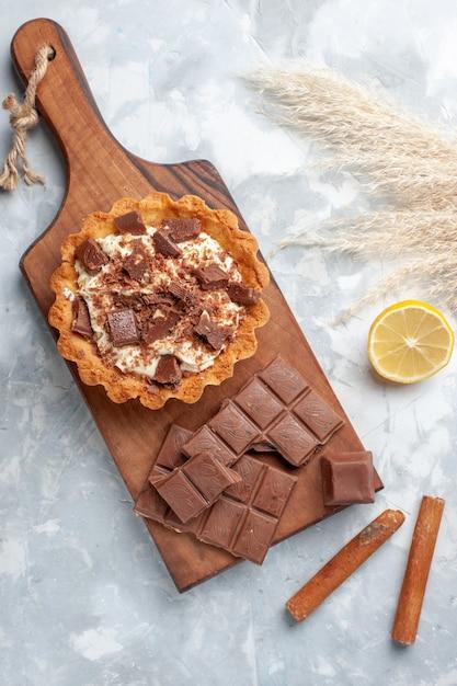 ライトデスクにチョコレートバーとシナモンのトップビュークリーミーな小さなケーキ甘いケーキシュガークリームチョコレート 無料写真