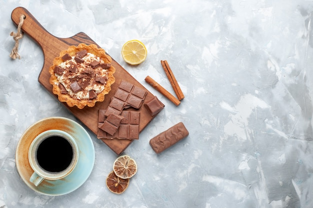 Вид сверху сливочный маленький торт с шоколадными батончиками и чаем с корицей на светлом столе сладкий торт сахарный крем шоколад Бесплатные Фотографии