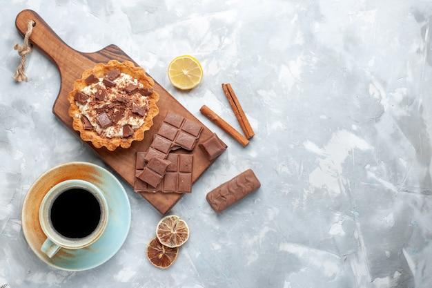 Top view creamy little cake with chocolate bars and cinnamon tea on light desk sweet cake sugar cream chocolate Free Photo