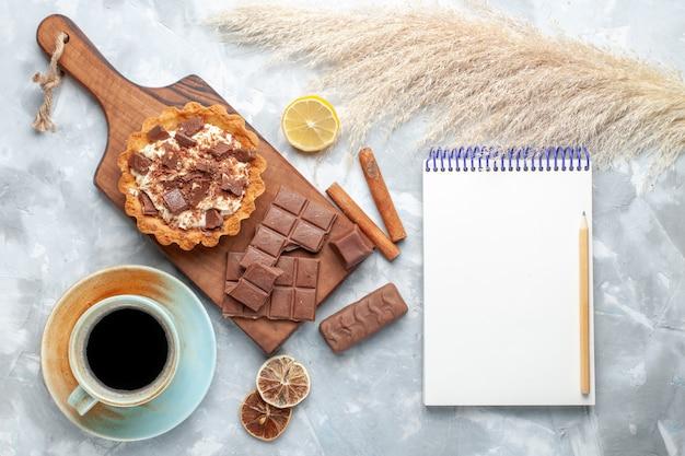 トップビュークリーミーな小さなケーキとチョコレートバーのメモ帳とシナモンのライトデスクの甘いケーキクリームチョコレート 無料写真