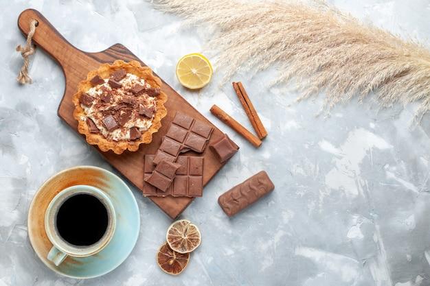 Вид сверху сливочный маленький торт с шоколадными плитками, чаем и корицей на светлом столе сладкий торт сахарный крем шоколад Бесплатные Фотографии