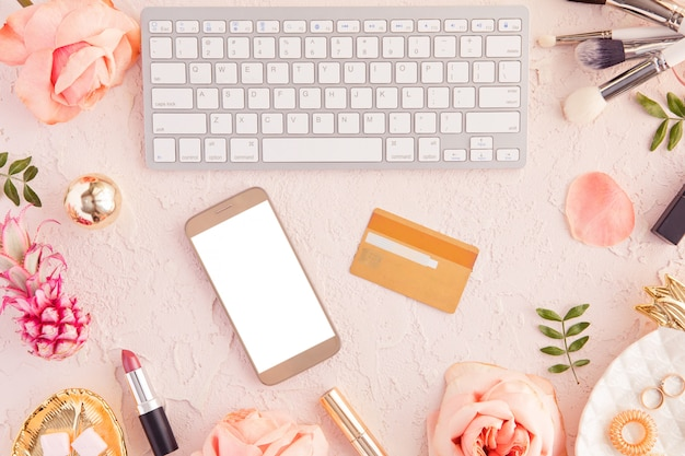 Top view of credit card and mobile phone with blank screen, online shopping and payment concept, female pastel pink workspace with flowers and laptop Premium Photo