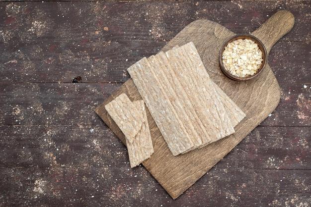 トップビューのクリスプとクラッカーは木製の机の上に長く形成 無料写真