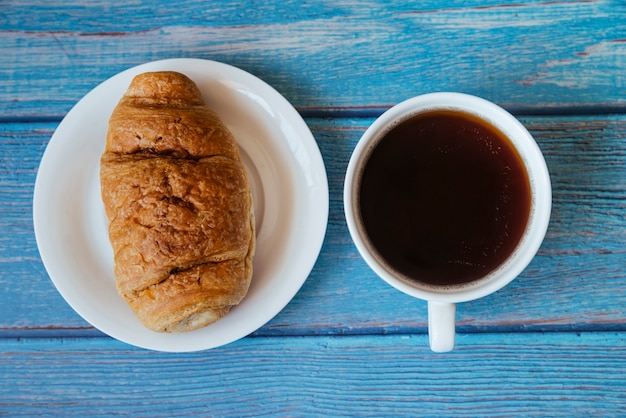 Top view croissant and coffee on wooden table Free Photo