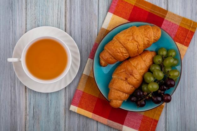 Vista dall'alto di croissant con l'uva nel piatto sul panno plaid e tazza di toddy caldo su fondo di legno Foto Gratuite