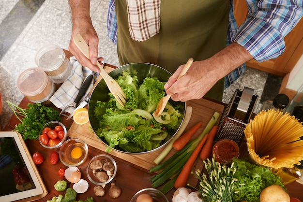 Top view of cropped man in cook apron mixing salad Free Photo