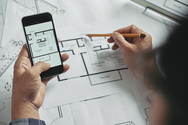 Top view of cropped unrecognizable person comparing paper and digital blueprints Free Photo