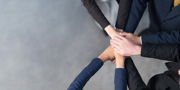 Top view, cropped view of a group of business people putting their hands together, friends with stack of hands showing unity, teamwork, success and unity concept Premium Photo