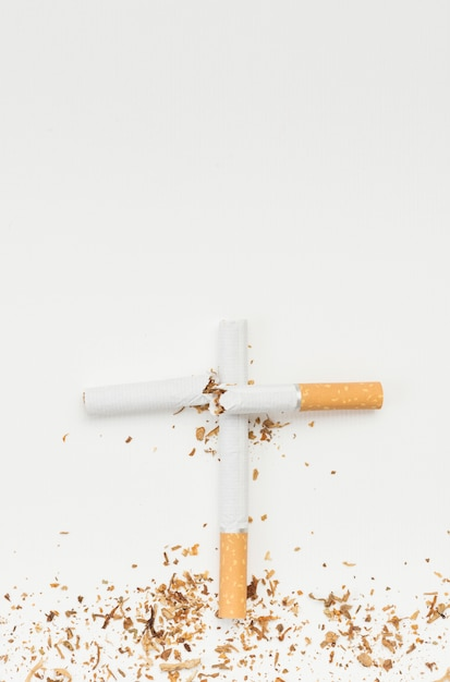 Top view of cross sign made from broken cigarette against white backdrop Free Photo