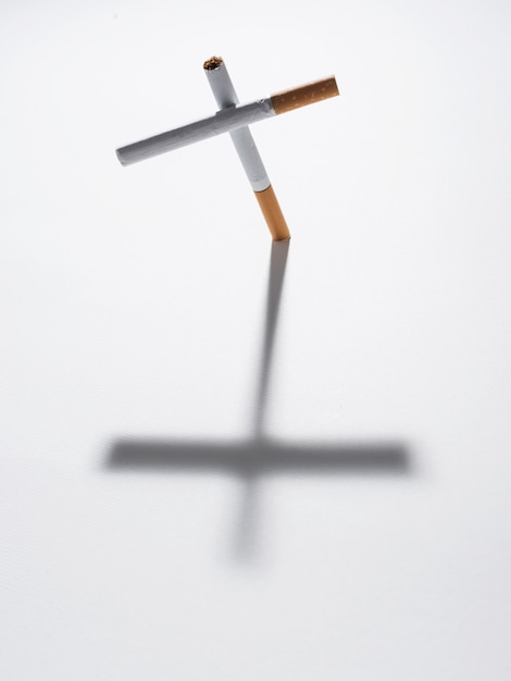 Top view of cross sign made from cigarette with it shadow on isolated on white background Free Photo