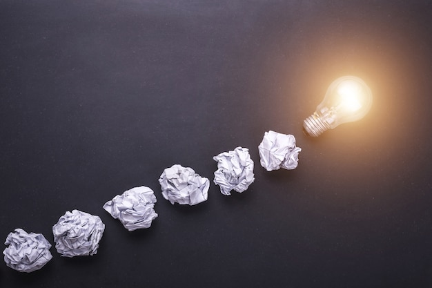 Top view crumpled white paper and light bulbs on black stone board Premium Photo
