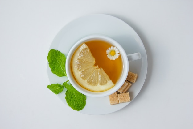 Top view a cup of chamomile tea with lemon, mint leaves, sugar on white surface. horizontal Free Photo
