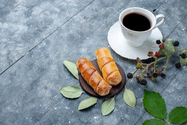 Vista dall'alto della tazza di caffè insieme a deliziosi braccialetti su zucchero di torta di pasticceria dolce in legno grigio Foto Gratuite