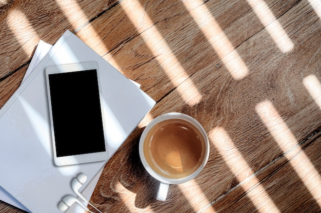 Top view cup of coffee and smartphone with blank screen on white book, copy space. Premium Photo