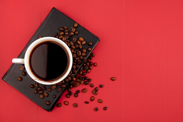 Top view of a cup of coffee with coffee beans on a red background with copy space Free Photo