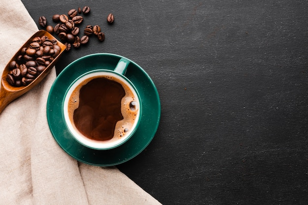 Top view cup of coffee with roasted beans Free Photo