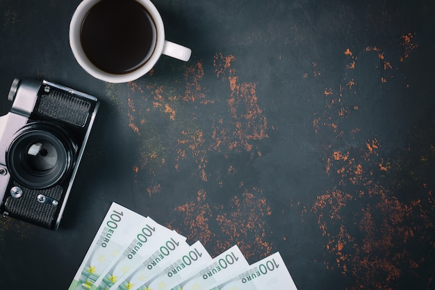 Top view a cup of coffee with vintage film camera and europe banknotes on rusty stone background Premium Photo